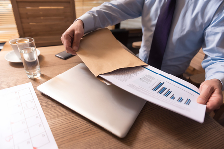 hard working: Business affairs. Close up of business documents with graphics and statistical data being taken out of the envelope by a hard working responsible male manager