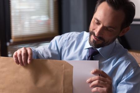 diligente: El papeleo. hombre diligente hermoso feliz que sostiene un sobre y mirando a los documentos, mientras que sacarlos de ella