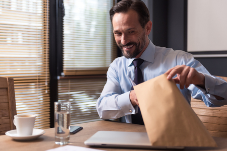 manhood: Work with documents. Optimistic delighted handsome man holding an envelope with documents and looking into it while sitting at the table Stock Photo