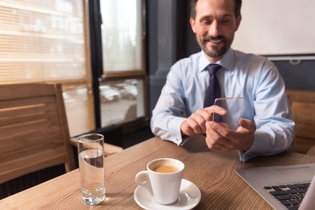 Modern technology. Nice cheerful pleasant man sitting at the table and holding a mobile phone while working in the office Stock Photo