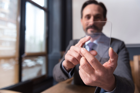 Innovative device. Good looking attractive successful businessman holding a smartphone and touching the sensor screen while sitting in the office Stock Photo