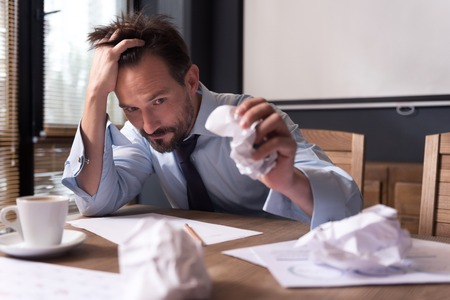 manhood: Need new ideas. Exhausted cheerless depressed man holding his head and crumpling a sheet of paper while dealing with a problem