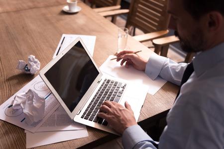 diligente: Necesito trabajar. Hombre serio en calma diligente con un lápiz y presionando los botones en el teclado mientras se trabaja en la computadora portátil