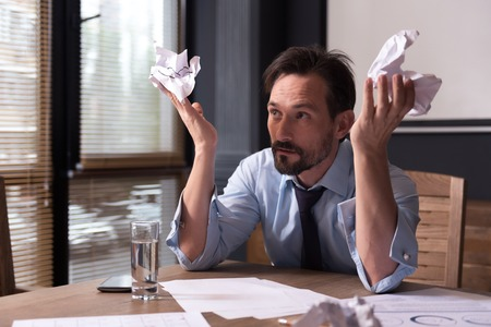 miserable: Do not know what to do. Sad miserable depressed man holding crumpled paper and throwing it up while working long hours on a project Stock Photo