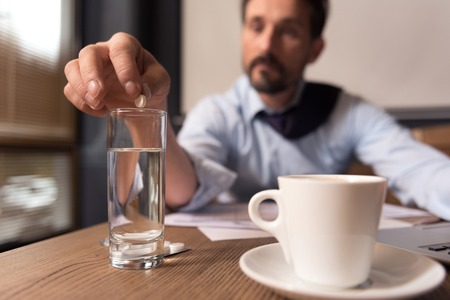 sedative: Taking sedatives. Selective focus of a small white sedative pill being put in the water by a cheerless exhausted depressed man while coping with stress Stock Photo