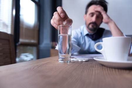 sedative: Need to calm down. Selective focus of a small white sedative pill being held by a stressed moody tired man while putting in into a glass of water