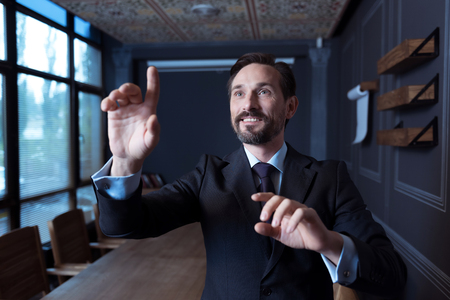 sensory: Involved in the activity. Happy positive confident man standing in front of a virtual sensory panel and pressing his hand to the screen while working in the virtual reality Stock Photo
