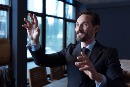 sensory: Technological achievements. Positive pleasant good looking man touching an imaginary sensory screen and smiling while standing in the conference room