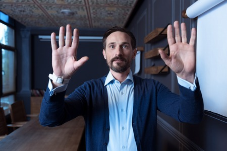 sensory: Invisible screen. Delighted nice positive man standing in the room and pressing hands to the virtual sensory panel while looking in front of him Stock Photo