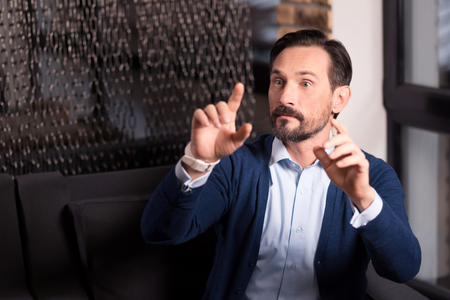 manhood: Futuristic technology. Serious brunette bearded man holding his hands in front of him and looking at the virtual images while working in the virtual reality Stock Photo