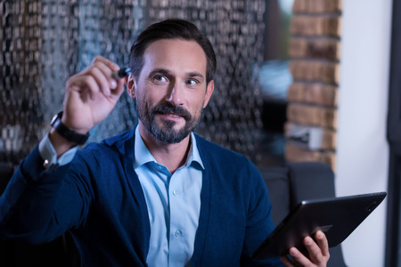 manhood: Technology era. Nice positive bearded man holding a tablet and looking at the virtual screen while writing something in it