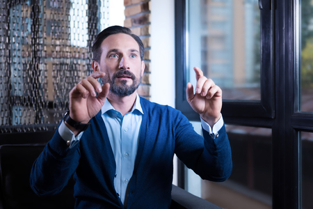 sensory: Virtual sensory screen. Nice handsome bearded man looking in front of him and touching the virtual sensory screen while sitting near the window
