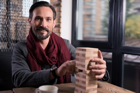 manhood: Pleasant entertainment. Happy handsome good looking man holding a wooden tower and smiling while playing blocks Stock Photo
