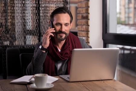 self employed: Involved in the conversation. Handsome successful self employed businessman looking at the laptop screen and smiling while speaking on the cell phone