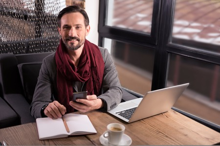 Wonderful mood. Positive happy nice man holding the cell phone and looking at you while working in the cafe Stock Photo