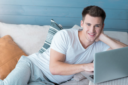 good mood: Good mood. Delighted handsome young man smiling and using laptop while lying on the sofa.
