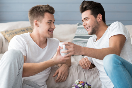 Coffee time. Happy attractive young gay couple smiling and drinking coffee while sitting on the floor.nking coffee.