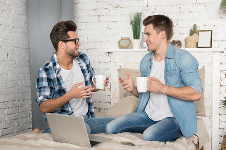 delightful: Delightful conversation. Two handsome joyful gay men having coffee and talking while sitting together on the bed.