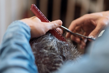 grey haired: Delicate work. Close up of man holding comb and scissors while doing haircut for grey haired man.