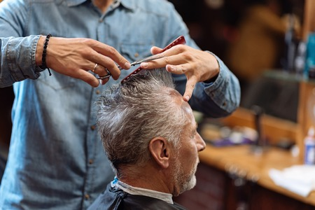 accurately: Doing accurately. Close-up of male hairdresser holding scissors and comb while doing haircut to senior man. Stock Photo