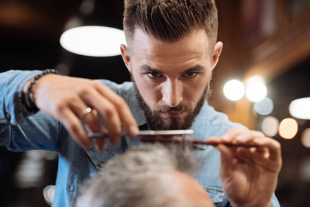 Serious attitude. Close-up portrait of nice young bearded hairstylist holding scissors and comb while cutting hair of his client.