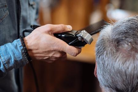 poquito: Poco a los lados. Vista trasera del hombre mayor de cabello gris que se recorta por el peluquero en la peluquería.