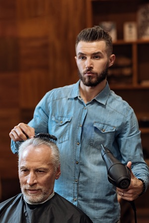 blow dryer: Im so fancy. Young handsome bearded hairstylist holding comb and blow dryer while standing near his senior client and looking forward. Stock Photo