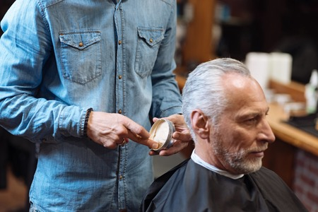 hair gel: Looking good already. Young male barber standing and holding jar with hair gel while his senior client waiting for him to start procedure.