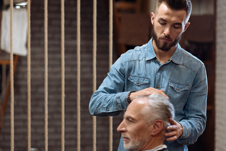 With pleasure. Nice handsome bearded hairstylist standing and touching head of senior client at barbershop.