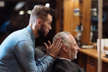 Last touches. Young handsome bearded hairdresser standing and styling hair of old man sitting at barbershop in front of mirror.