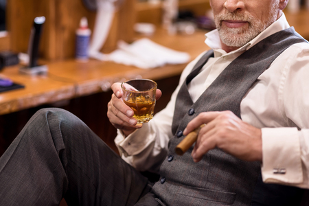 mafioso: Showing off. Close up of senior bearded man wearing luxury suit sitting on armchair with whiskey glass and cigar. Stock Photo