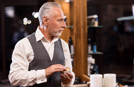 hair gel: Getting ready. Side view of nice senior bearded man standing and holding jar with hair gel in front of mirror. Stock Photo