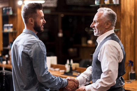 two generations: Two generations. Solid senior man standing and shakings hands with handsome young hairstylist at barbershop.