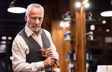 manhood: High status. Portrait of elegant handsome senior bearded man standing with whiskey glass and cigar at barbershop. Stock Photo
