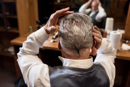 beautify: Beautify yourself. Close up back view of senior gentle man styling his grey hair himself at barbershop. Stock Photo