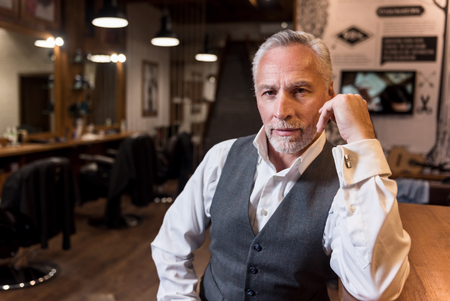 glance: Intent glance. Portrait of attractive senior businessman wearing luxury suit sitting at bar counter, leaning on arm and looking forward.