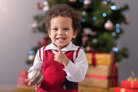 curly headed: Preparing to celebrate. Adorable cute happy boy standing in front of Christmas tree and smilling while holding a Christmas decoration