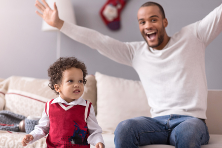 curly headed: I love my family. Charming pretty small boy standing near the sofa and smiling while having fun with his father Stock Photo