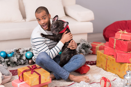 manhood: My best friend. Pleasant good looking bearded man sitting among Christmas presents and holding his dog while having a great time Stock Photo