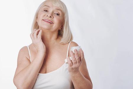 Soin de la peau. Belle femme âgée agréable et agitée, tendant la crème sur le cou en tenant une bouteille anti-âge