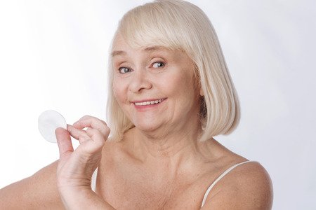 I want to look young. Pleasant positive elderly woman holding her hand up and having a cotton pad in it while wanting to look young