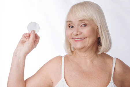 I care about my skin. Nice delighted aged woman holding a cotton pad and smiling while cleaning her face