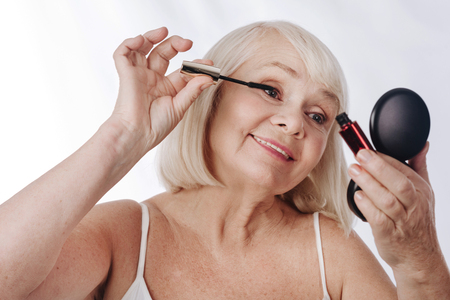 Decorative cosmetics. Good looking content aged woman applying mascara and looking into the mirror while using decorative cosmetics Stock Photo