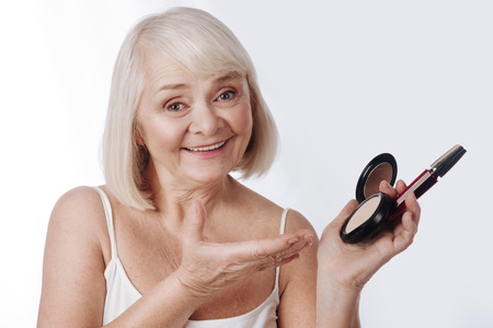 Stay beautiful. Nice pleasant retired woman holding face powder and mascara and pointing at it while looking at you