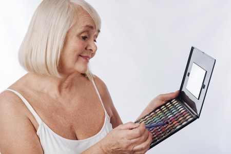 wide choice of colour good looking cheerful senior woman holding