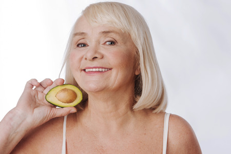 doze: Doze of vitamins. Joyful positive aged woman standing against the white background and smiling while holding half of the avocado Stock Photo