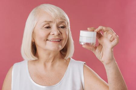 Anti invecchiamento della pelle prodotti. Piacevole affascinante donna senior in possesso di un flacone di crema lifting della pelle e guardando che durante l'utilizzo di cosmetici anti-età Archivio Fotografico