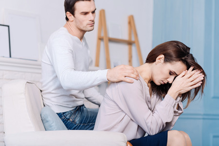 We will deal with it. Young gloomy woman sitting in the arm chair and holding her hands on the forehead while her husband comforting her