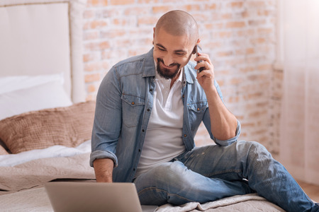 Happy to hear you. Cheerful delighted bearded man sitting in the bedroom in front of the laptop while expressing happiness and talking over the phone