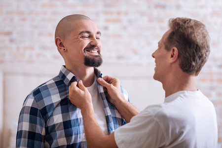 get ready: I enjoy caring about you. Cheerful positive smiling non-traditional man standing in the bedroom and helping his partner to get ready while expressing happiness Stock Photo